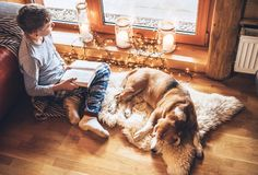 Boy reading book on the floor near slipping his beagle dog on sheepskin in cozy home atmosphere. Peaceful moments of cozy home. Concept image stock photos