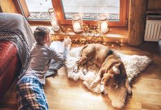 Boy reading book on the floor near slipping his beagle dog on sheepskin in cozy home atmosphere. Peaceful moments of cozy home. Concept image stock images