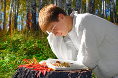 Boy Reading Book in Forest Stock Images