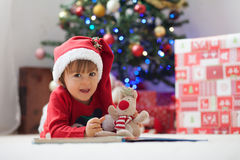 Boy, reading a book in front of a Christmas tree. Stock Photos