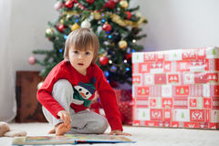 Boy, reading a book in front of a Christmas tree. Stock Image