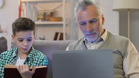 Boy reading book, grandpa using laptop at home, education in different age