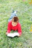 Boy reading book on grass Royalty Free Stock Photos