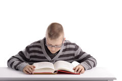 Boy reading a book at his desk Stock Photography