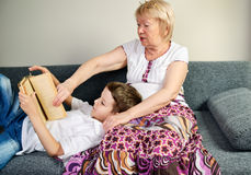 Boy reading a book with his grandmother indoor Royalty Free Stock Photography
