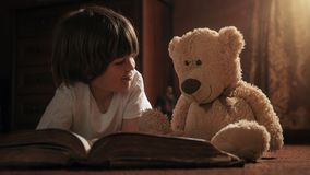 Boy reading book with his teddy bear royalty free stock image