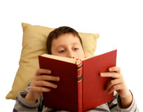 Boy reading a book. Boy at home, reading a book. Isolated on white Royalty Free Stock Photos