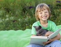 Boy reading book with kitten in the yard, child with pet reading. Magazine on the grass in the park royalty free stock image