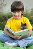 Boy reading book with kitten in the yard, child with pet reading Stock Image