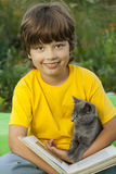 Boy reading book with kitten in the yard, child with pet reading Stock Photo