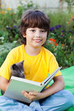 Boy reading book with kitten in the yard, child with pet reading Royalty Free Stock Image