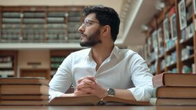 Boy Reads Book. Boy reading a book in the library, young bearded man with wavy black hair helping to focus on the text with the fingers, thinking about received stock video footage