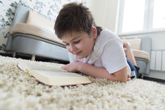 Boy reading a book while lying on  carpet in the room Royalty Free Stock Image
