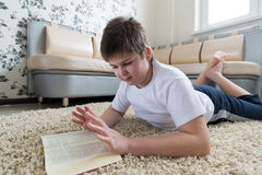 Boy reading a book while lying on  carpet in the room Stock Photo