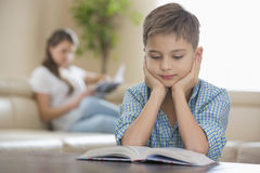 Boy reading book with mother in background at home Stock Photography