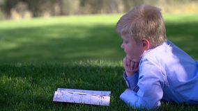 Boy reading book outdoors stock video footage
