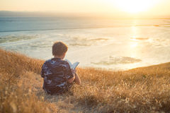 Boy reading book outside at sunset Royalty Free Stock Photo