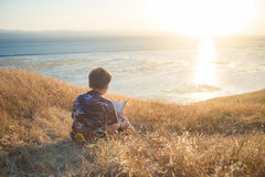 Boy reading book outside at sunset. Boy reading book in yellow grass high in the hills, watching beautiful sunset above Bay Area, rear view royalty free stock photos