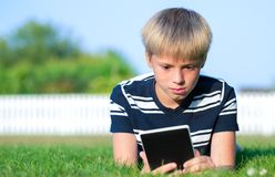 Boy reading a book in the park. The boy reads the e-book, lying on the grass Stock Image