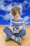 Boy reading book seating on the floor with cloud Stock Photos