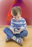 Boy reading book seating on the floor with Royalty Free Stock Photo