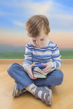 Boy reading book seating on the floor with sunrise Royalty Free Stock Image