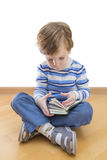 Boy reading book seating on the floor on white Royalty Free Stock Photos