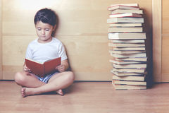 Boy reading a book. Sitting on the floor Stock Images