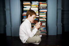 boy reading book sitting on the floor Royalty Free Stock Image
