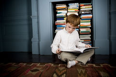 boy reading book sitting on the floor Stock Photo
