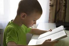 Boy reading a book sitting at the table royalty free stock photos