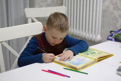 Boy reading a book. Boy sitting at a table and reading a book Stock Images