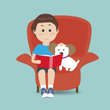 Boy reading the book on the sofa with his dog Stock Image