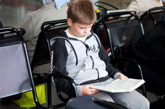Boy reading  book at the station Stock Image