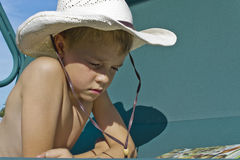 Boy reading a book. Boy in a straw hat reading a book Royalty Free Stock Photos