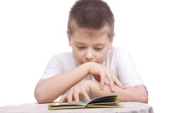 Boy reading book at table Stock Photography