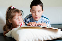 Boy reading a book to his sister Royalty Free Stock Images