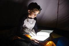 Boy reading a book with torch at night Stock Photography