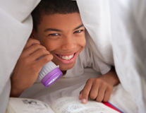 Boy Reading Book With Torch Under Duvet Stock Image