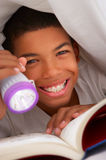 Boy Reading Book With Torch Under Duvet Royalty Free Stock Photography