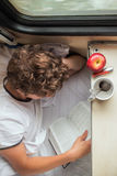 Boy reading a book on the train Stock Photos