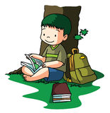 Boy reading book under tree Stock Photography