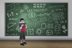 Boy reading book with written chalkboard Stock Photos