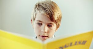 Boy reading english book closeup. Handsome preteen schoolboy reading english book and smiling, modern education, foreign languages stock footage