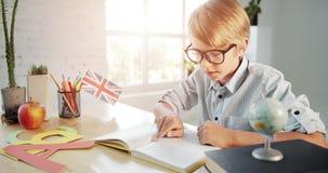 Boy Reading English Textbook. Cute preteen schoolboy in eyeglasses reading english textbook in classroom, modern education, knowledge stock video