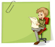 A boy reading in front of a big paper with a clip Stock Photography