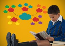Boy reading in front of colorful clouds on yellow background. Digital composite of Boy reading in front of colorful clouds on yellow background Royalty Free Stock Images