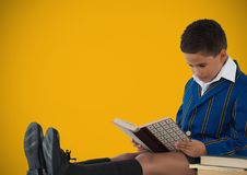 Boy reading in front of yellow background. Digital composite of Boy reading in front of yellow background Stock Photography