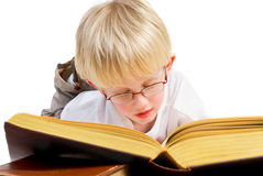 Boy is reading a good book. Little blond boy is reading a thick good book Stock Photo