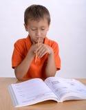 Boy reading homework. At the desk Stock Images